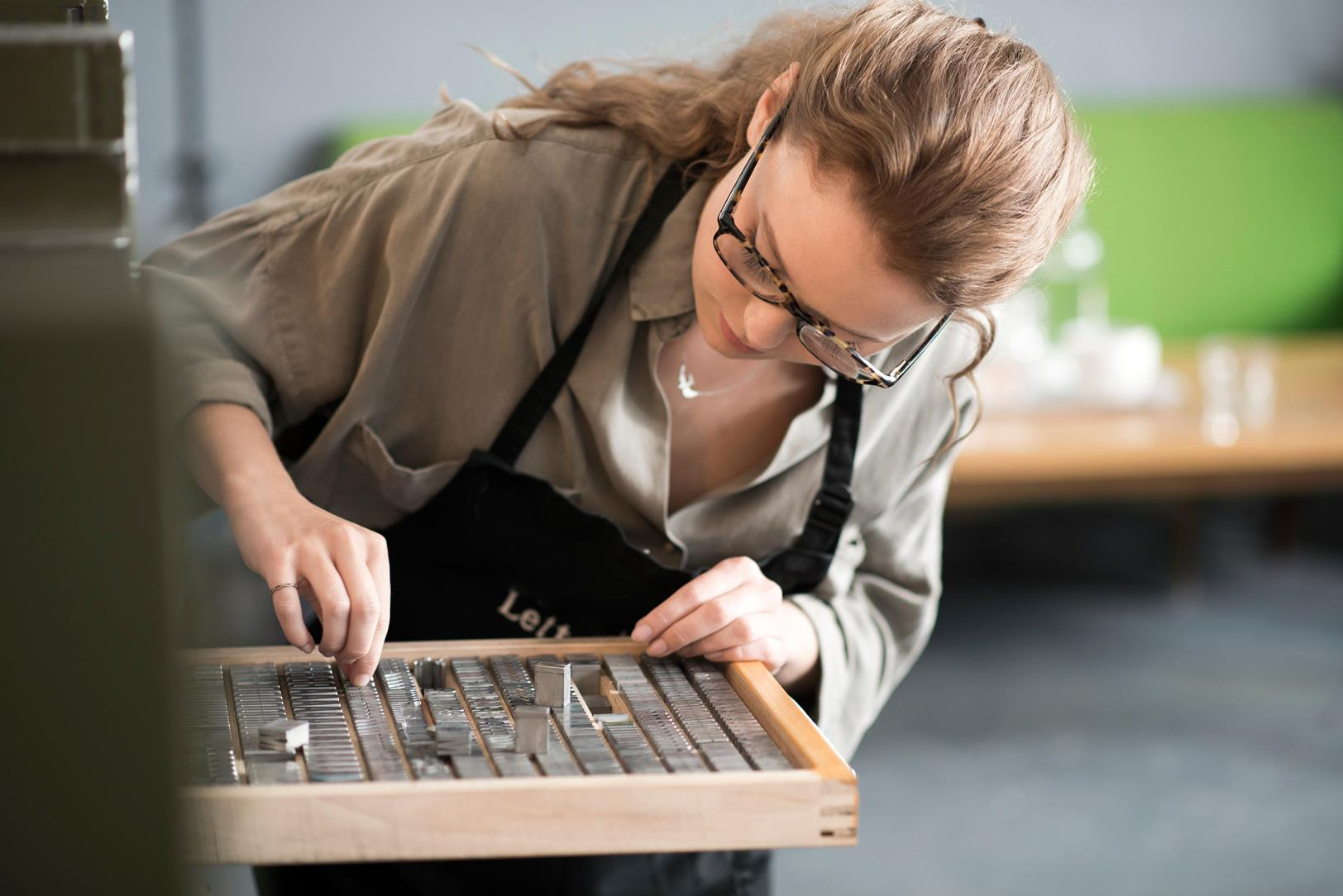 Woman selecting print blocks for a letterpress